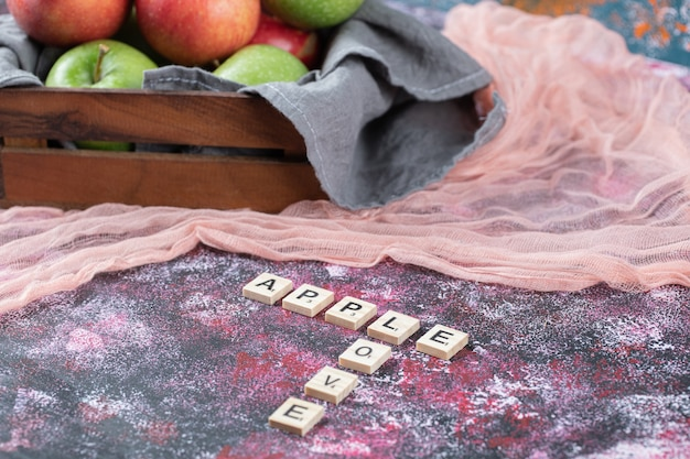 Maçãs em uma bandeja de madeira rústica sobre um pano de prato