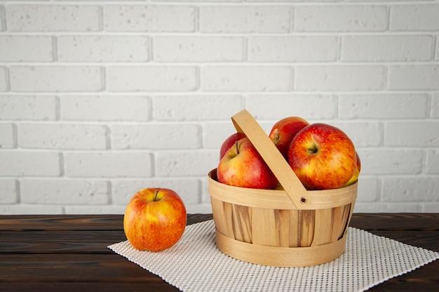 Maçãs em uma cesta de madeira em uma superfície de madeira