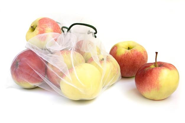 Maçãs em uma sacola reutilizável em um fundo branco.