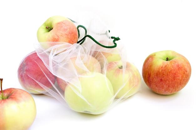 Maçãs em uma sacola reutilizável em um fundo branco