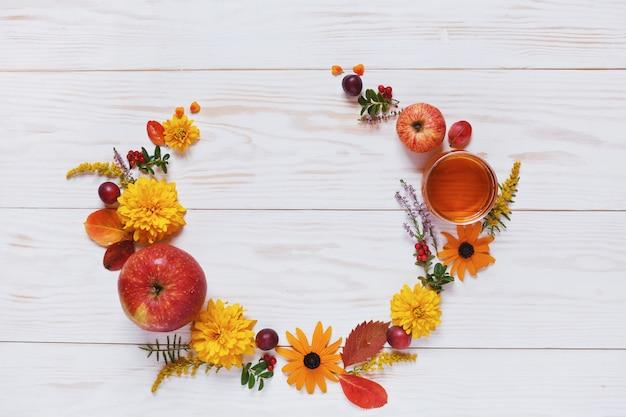 Maçãs, flores e mel com espaço de cópia formam uma decoração floral