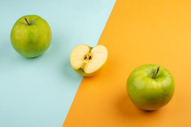 Maçãs frescas azedo maduro no chão laranja e azul gelo