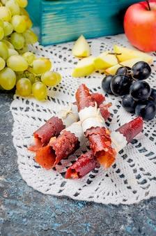Maçãs frescas colhidas e uvas e frutas pastille em fundo escuro