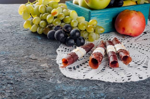 Maçãs frescas colhidas e uvas e pastilha de frutas no escuro