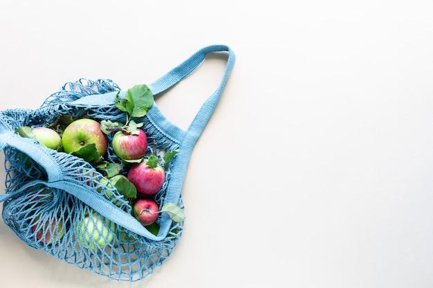Maçãs frescas em uma malha de sacola de compras. resíduos zero, nenhum conceito de plástico. uma dieta saudável e desintoxicação. colheita de outono. camada plana, vista superior.