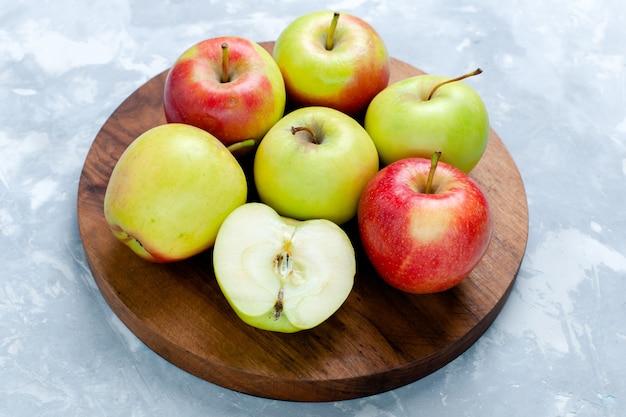 Maçãs frescas, frutas maduras e maduras em frente a foto colorida vitamina branca de frutas