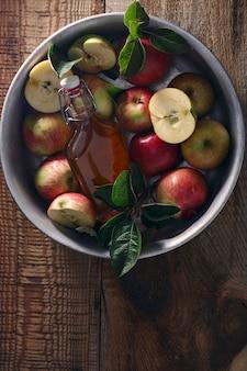 Maçãs frescas maduras e vinagre de maçã. cidra de maçã em uma garrafa de vidro e maçãs frescas em uma velha mesa de madeira. fundo escuro. vista do topo.