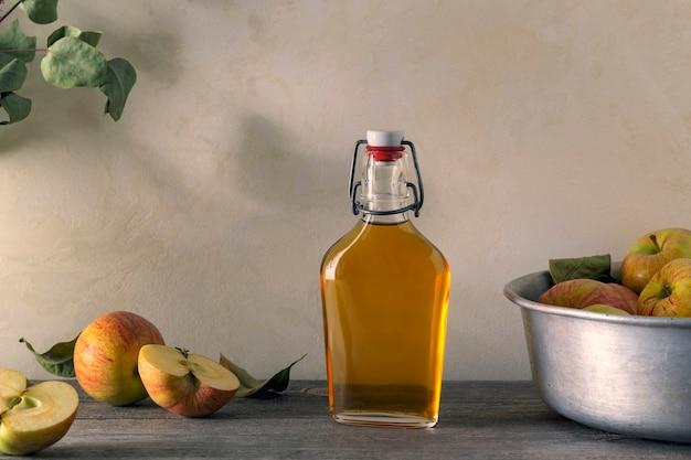 Maçãs frescas maduras e vinagre de maçã. cidra de maçã em uma garrafa de vidro e maçãs frescas. fundo claro.