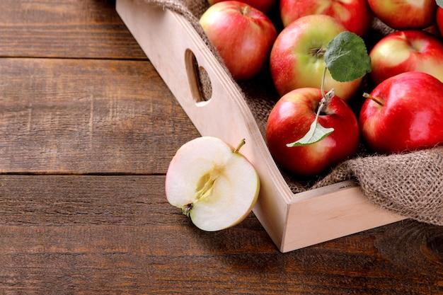 Maçãs frescas maduras em uma bandeja de madeira sobre um fundo de madeira