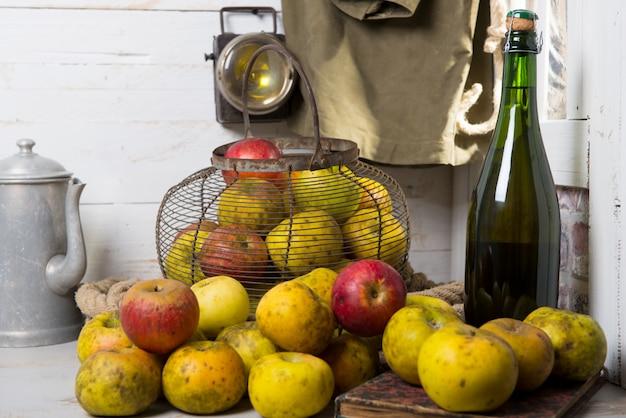 Maçãs frescas orgânicas com garrafa de sidra da normandia