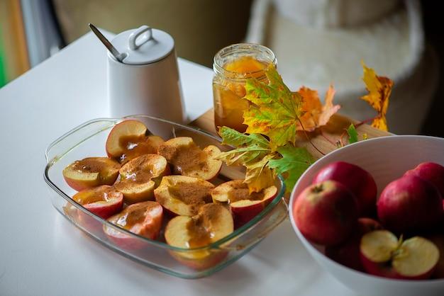 Maçãs fritas com canela e mel decoradas com folhas coloridas de outono na mesa branca