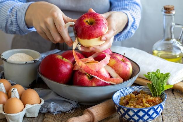 Maçãs lavadas com gotas de água em uma tigela. descasque maçãs maduras e suculentas. ingredientes para o strudel de maçã. processo de torta. torta de maçã em casa descasque as maçãs vermelhas
