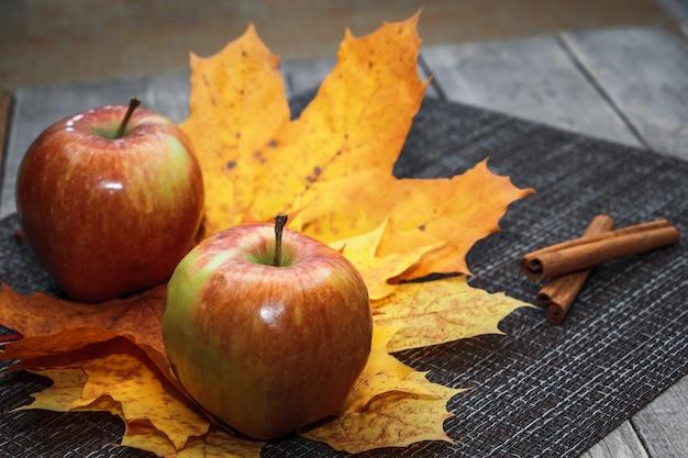 Maçãs maduras de outono em um fundo de folhas de laranja