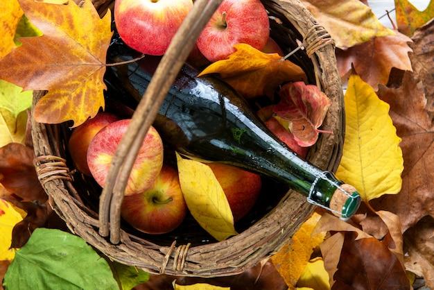 Maçãs na cesta e garrafa de cidra da normandia