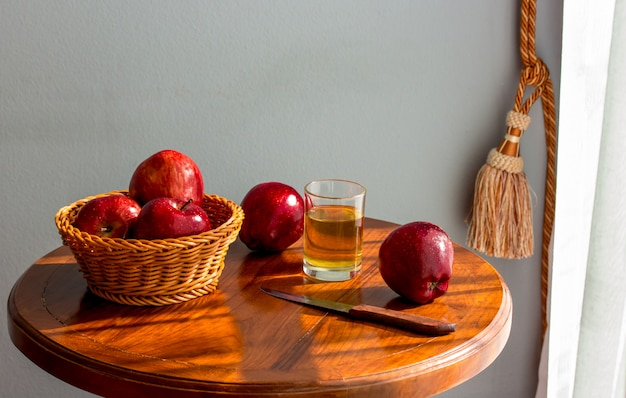 Maçãs na mesa, suco de maçã, manhã no quarto ao lado da janela.