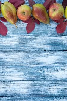 Maçãs, peras e folhas de outono no fundo de madeira. fundo de outono