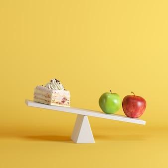 Maçãs que derrubam a balancê com o bolo na extremidade oposta no fundo pastel. idéia de comida mínima.