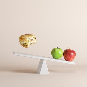 Maçãs que derrubam a balancê com os bergers de flutuação na extremidade oposta no fundo pastel.