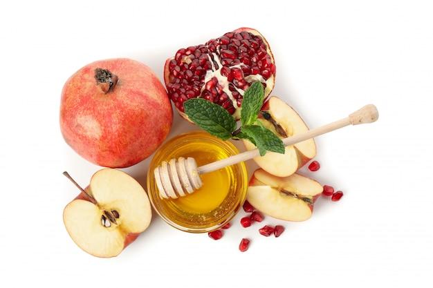 Maçãs, romã e mel isolados no branco. tratamento natural