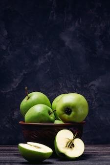 Maçãs são verdes em uma tigela e uma maçã fatiada