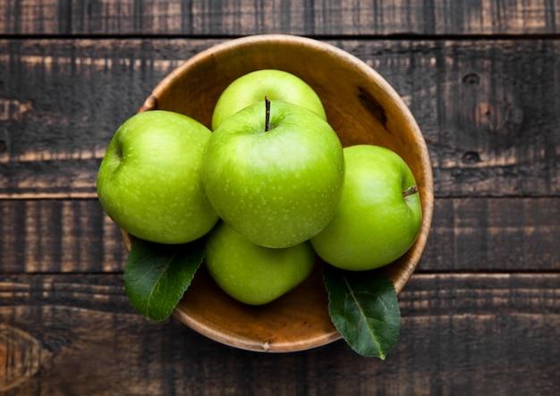 Maçãs saudáveis orgânicas verdes em tigela na placa de madeira