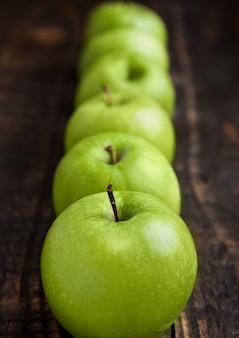 Maçãs saudáveis orgânicas verdes na placa de madeira