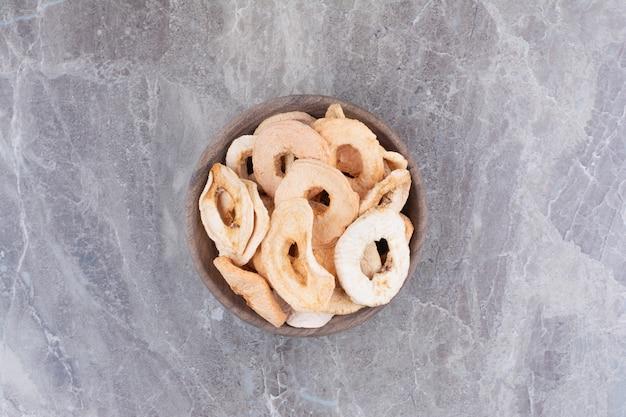 Maçãs saudáveis secas na placa de madeira.