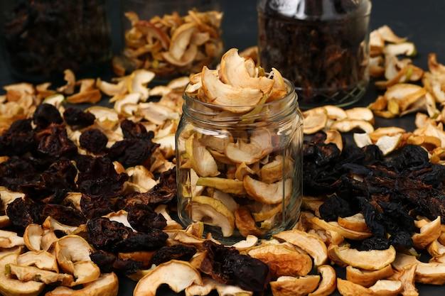 Maçãs secas caseiras, ameixas e peras em potes de vidro