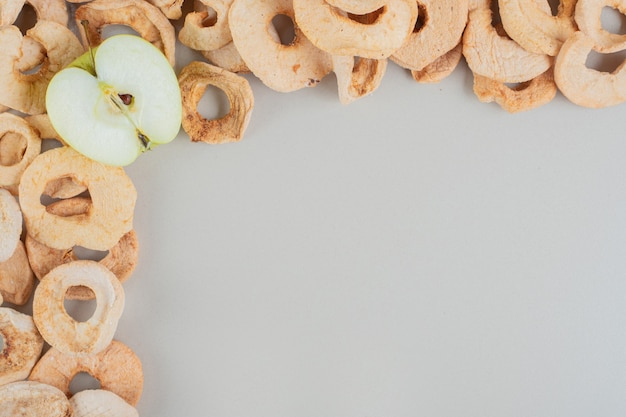 Maçãs secas com uma fatia de maçã fresca.