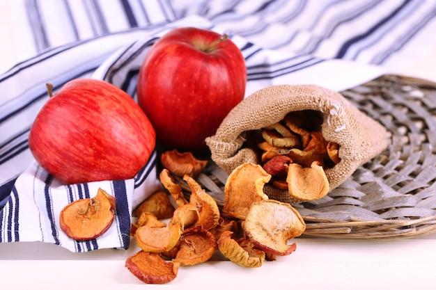 Maçãs secas e maçãs frescas no guardanapo na mesa de madeira branca