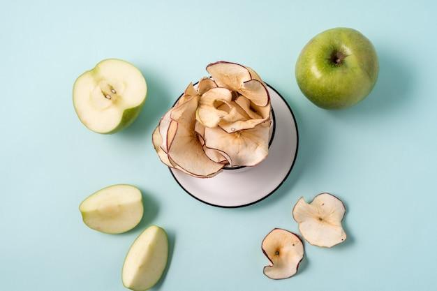 Maçãs secas em um copo e maçãs frescas sobre azul claro.