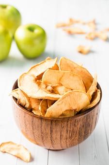 Maçãs secas em uma tigela de madeira maçãs verdes maduras em cima da mesa