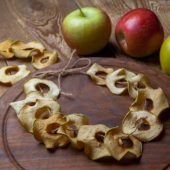 Maçãs secas na tábua redonda e maçãs frescas na mesa de madeira