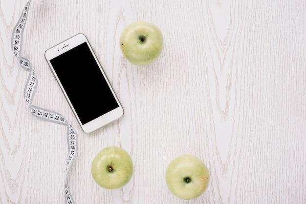 Maçãs, smartphone e fita de medição