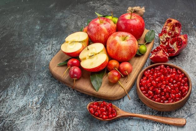 Maçãs tigela de romã maçãs cerejas na tábua