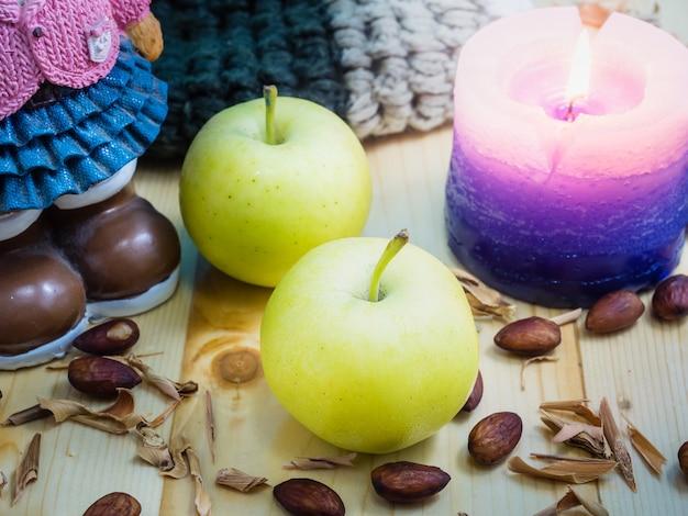 Maçãs, velas na mesa, madeira. quando o inverno todo mundo precisa de calor.