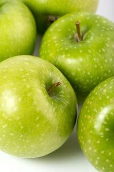 Maçãs verde todo perfeitamente formado maduro suculento maduro em um branco