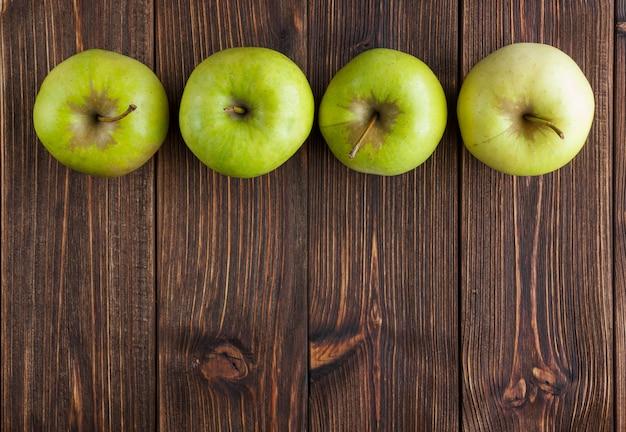 Maçãs verdes alinhadas em uma vista superior do plano de fundo de madeira, espaço livre para o seu texto