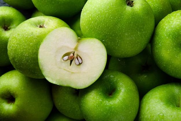 Maçãs verdes closeup, meia maçã em maçãs verdes inteiras