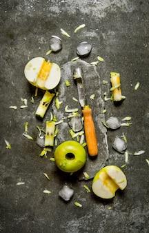 Maçãs verdes com faca e gelo. sobre uma mesa rústica de pedra. vista do topo