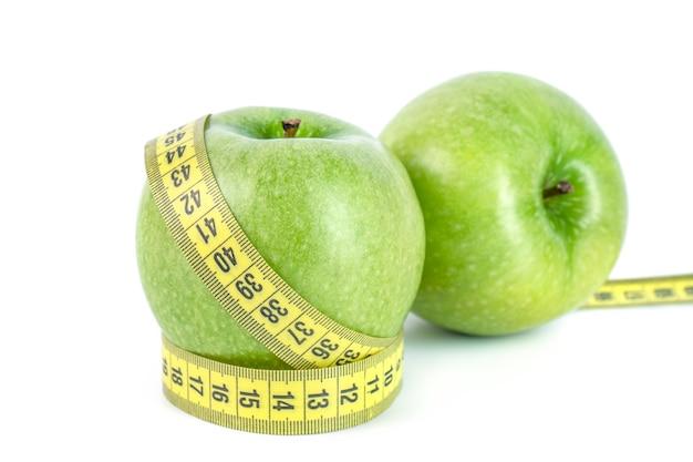 Maçãs verdes com fita métrica em fundo branco no conceito de saudável e dieta.