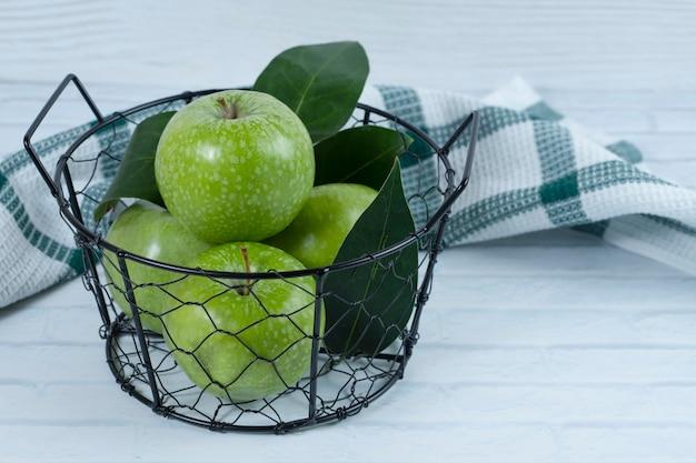 Maçãs verdes com folhas na cesta preta metálica colocada sobre fundo branco. foto de alta qualidade