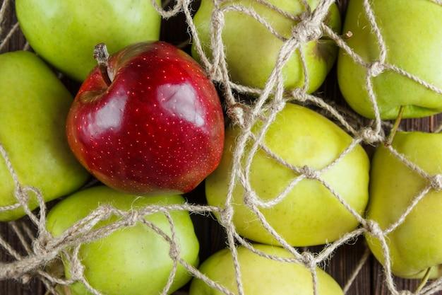 Maçãs verdes com maçã vermelha em cima em um saco de rede em uma vista superior do plano de fundo de madeira