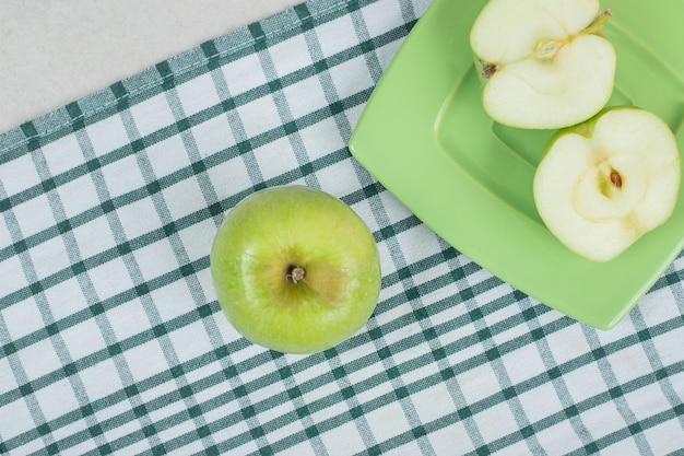 Maçãs verdes cortadas pela metade no prato verde