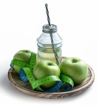 Maçãs verdes e suco de maçã com fita métrica para controlar o peso na dieta.