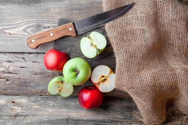 Maçãs verdes e vermelhas cortadas ao meio com faca, madeira e pano vista superior em um fundo escuro de madeira