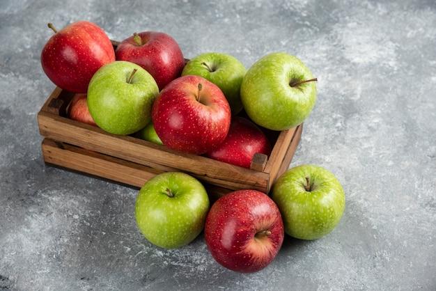 Maçãs verdes e vermelhas deliciosas frescas em caixa de madeira.