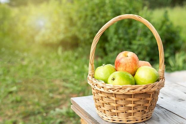 Maçãs verdes e vermelhas na cesta de vime na mesa de madeira grama verde na jardim hora da colheita sun flare