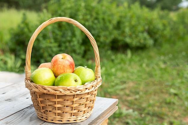 Maçãs verdes e vermelhas na cesta de vime na mesa de madeira grama verde no jardim tempo de colheita