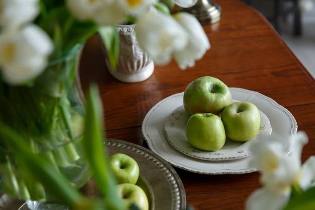 Maçãs verdes em um prato de porcelana sobre a mesa